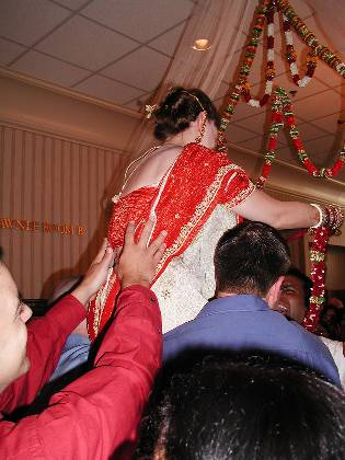 Lifting Cindy so Neerav can't place the garland on her head