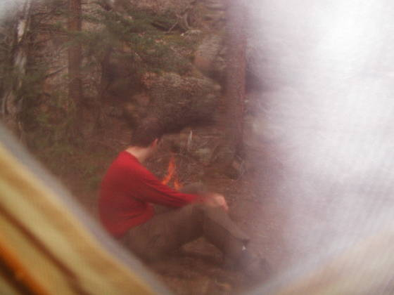 Brian tending the fire, through the tent window