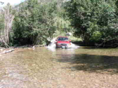 The Land Cruiser plunges into the second, deeper, stream crossing (1 of 4)