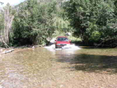 The Land Cruiser plunges into the second, deeper, stream crossing (2 of 4)