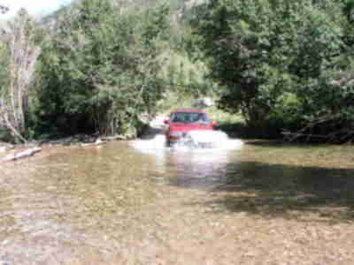 The Land Cruiser plunges into the second, deeper, stream crossing (3 of 4)