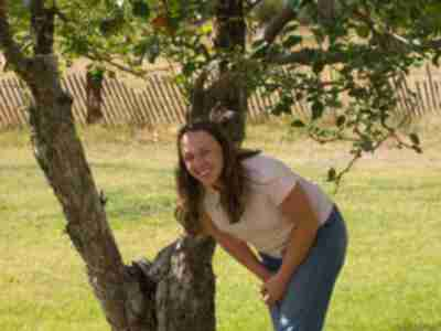 Lisa grabbing apples from an orchard tree