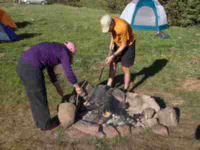 Lisa and Lonny work to dig all of the meat and trash out of the fire that the previous camp occupants left