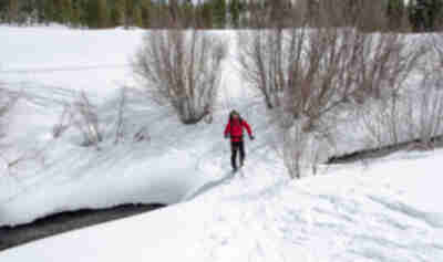 Noah crosses the snow bridge across the Eagle River