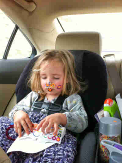 Amy enjoys some stickers in the car