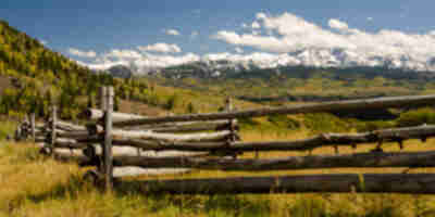 A fence backed by snowcapped peaks
